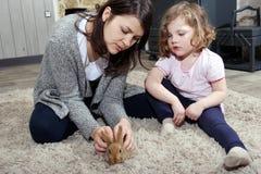 Madre e figlia che giocano con un coniglietto fotografie stock