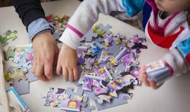 Madre e figlia che giocano insieme i giochi di puzzle fotografia stock