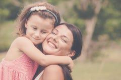 Madre e figlia che giocano sull'erba al tempo di giorno Immagine Stock