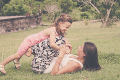 Madre e figlia che giocano sull'erba al tempo di giorno Immagine Stock Libera da Diritti