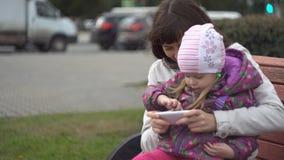 Madre e figlia che giocano sullo smartphone che si siede sul banco all'aperto stock footage