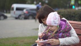 Madre e figlia che giocano sullo smartphone che si siede sul banco all'aperto archivi video
