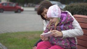Madre e figlia che giocano sullo smartphone che si siede sul banco all'aperto video d archivio