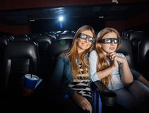 Madre e figlia che guardano film 3D nel teatro Immagine Stock