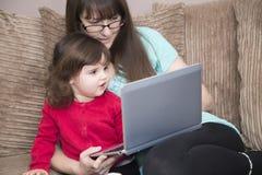 Madre e figlia che imparano con un computer portatile fotografie stock
