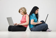 Madre e figlia che lavorano ai computer portatili Immagini Stock Libere da Diritti