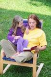 Madre e figlia che leggono un libro fotografia stock