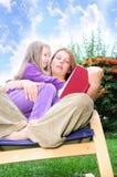 Madre e figlia che leggono un libro immagini stock libere da diritti