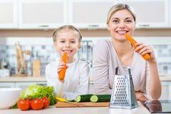 Madre e figlia che mangiano carota Immagine Stock