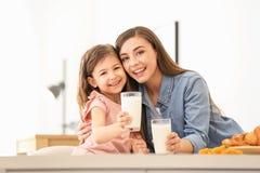 Madre e figlia che mangiano prima colazione con latte immagine stock