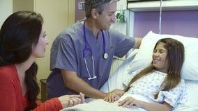 Madre e figlia che parlano con l'infermiere maschio nella stanza di ospedale archivi video
