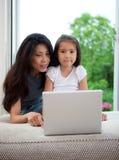 Madre e figlia che per mezzo del calcolatore Fotografia Stock