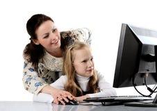 madre e figlia che per mezzo del calcolatore Immagine Stock