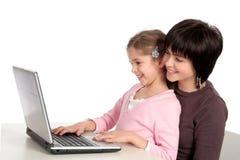 Madre e figlia che per mezzo del computer portatile Fotografie Stock Libere da Diritti