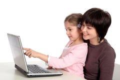 Madre e figlia che per mezzo del computer portatile