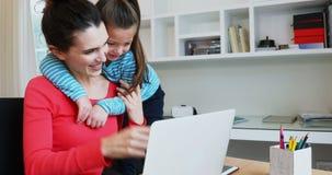 Madre e figlia che per mezzo del computer portatile 4k video d archivio
