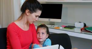 Madre e figlia che per mezzo del computer portatile 4k stock footage