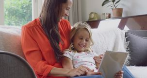 Madre e figlia che per mezzo della compressa digitale sul sofà a casa 4k stock footage
