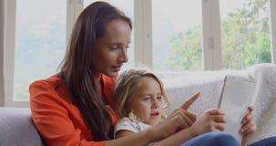 Madre e figlia che per mezzo della compressa digitale sul sofà a casa 4k video d archivio