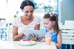 Madre e figlia che per mezzo insieme del computer della compressa Immagini Stock