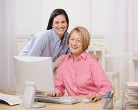 Madre e figlia che propongono con il calcolatore Immagine Stock