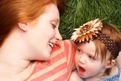 Madre e figlia che risiedono nell'erba Immagine Stock Libera da Diritti