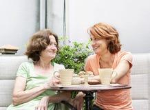 Madre e figlia che si rilassano nel cortile Immagine Stock