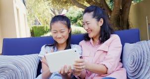 Madre e figlia che si rilassano sullo strato e che per mezzo della compressa digitale 4k stock footage