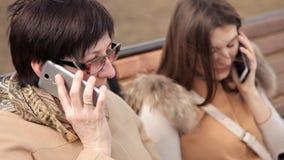 Madre e figlia che si siedono nel parco su un banco e che parlano su un telefono cellulare Famiglia, tempo, passeggiata archivi video
