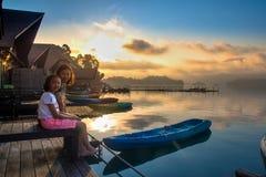 Madre e figlia che si siedono sul lago naturale della zattera nel mattino Fotografia Stock