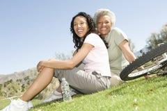 Madre e figlia che si siedono sull'erba in parco Fotografia Stock