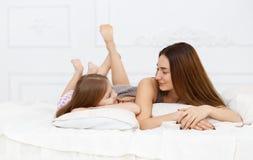 Madre e figlia che si trovano su un letto bianco Fotografie Stock