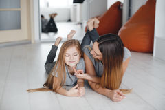 Madre e figlia che si trovano sul pavimento e sullo sguardo ad a vicenda Fotografia Stock Libera da Diritti