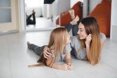 Madre e figlia che si trovano sul pavimento e sullo sguardo ad a vicenda Immagine Stock Libera da Diritti