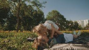 Madre e figlia che si trovano sul prato inglese Famiglia divertendosi nel parco della città all'aperto stock footage