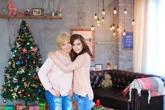 Madre e figlia che stanno parallelamente, sorridenti e posanti, g Fotografie Stock
