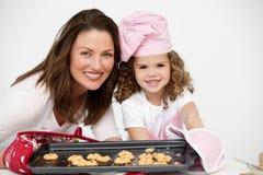 Madre e figlia che tengono una zolla con i biscotti Fotografie Stock