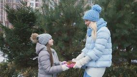 Madre e figlia con i regali in mani ai precedenti dell'abete archivi video