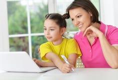 Madre e figlia con il computer portatile Fotografia Stock Libera da Diritti