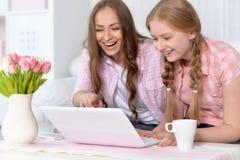 Madre e figlia con il computer portatile Fotografie Stock Libere da Diritti