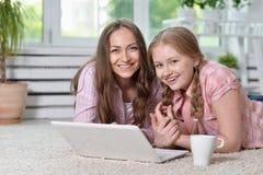 Madre e figlia con il computer portatile Fotografia Stock