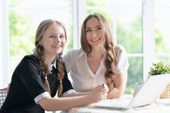 Madre e figlia con il computer portatile Immagini Stock