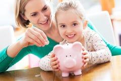 Madre e figlia con la banca piggy Immagine Stock Libera da Diritti
