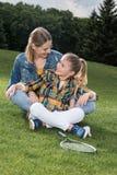 Madre e figlia con la racchetta di volano che si siede sull'erba e che si sorride Immagine Stock Libera da Diritti