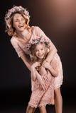 Madre e figlia in corone floreali che abbracciano e che sorridono alla macchina fotografica Fotografia Stock