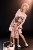 Madre e figlia in corone floreali che abbracciano e che sorridono alla macchina fotografica Immagini Stock Libere da Diritti