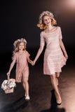 Madre e figlia in corone floreali che camminano con il canestro del fiore Immagine Stock