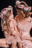Madre e figlia in corone floreali che si esaminano reciprocamente e risata Immagine Stock