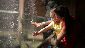Madre e figlia del cutie che gioca con la piccola cascata Stanno avendo molto divertimento al giorno di madri insieme stock footage