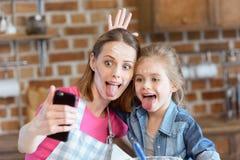 Madre e figlia dello smorfia che fanno selfie mentre cucinando a casa Fotografie Stock Libere da Diritti